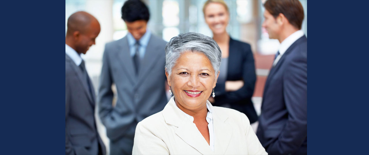 Female professional in front of a blurred group of other professionals talking in background